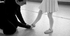 adult putting ballet shoe on kid