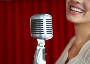 Beautiful smiling woman singing with the microphone