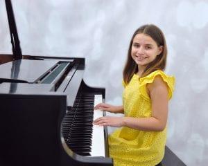 Girl playing piano, wearing yellow