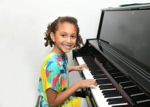 Girl playing piano happily